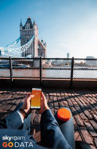 person holding skyroam solis looking out at the london bridge